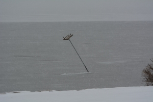 The bent pole has been spun around by the ice and wind to the north