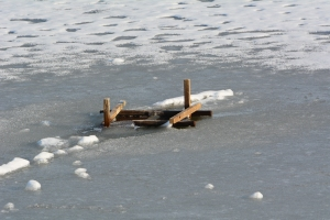 The pole and platform have fallen into the ice.  The platform is mangled and the pole has sunk to the bottom.